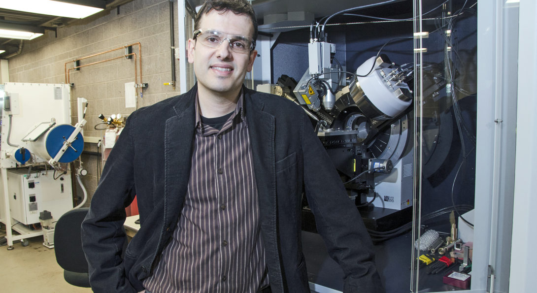 Prof. Cabana stands by an X-ray diffractometer, an instrument that characterized energy storage materials.